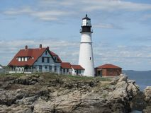 New England fyr - Portland Head ljus på en stenig kust i Portland Maine arkivfoton