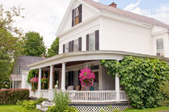 New England house porch. An old New England house with a wrap-around porch and landscaping. Waterbury, Vermont