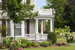 New England house porch. An old New England house with a large white porch, bay windows, and flowers for landscaping Royalty Free Stock Photos