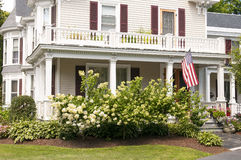 New England house porch. An old New England house with a large white porch, bay windows, and flowers for landscaping Stock Photos