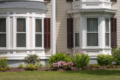 New England house windows. An old New England house with bay windows and bow windows, and flowers for landscaping Royalty Free Stock Photography