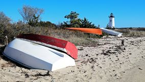 New England Lighthouse with Colorful fishing boats on the shore. Colorful fishing boats line the shore with a white New England lighthouse in the distance royalty free stock photos