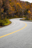 New England Road. A curved New England road during the fall with bright foliage Royalty Free Stock Photography