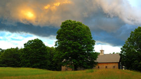 New England Style Long Barn under early evening clouds. Green and golden grass, green trees,brown wooden barn, blue sky, thunderclouds Royalty Free Stock Photo