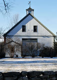 New England white barn with green trim one bright early December day. Multi story van with cupola, blue sky, snow covered royalty free stock photos