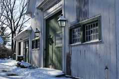 New England White Barn after a snow storm with Green Doors and Green Trim. Dirty, black lanterns, multi-pane windows, sunny, snow covered drive royalty free stock photo