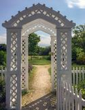 New England white wooden arbor garden gates and sunlit path. Closeup of New England white wooden arbor gates and sunlit path to the garden on summer morning in Stock Photos