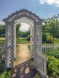 New England white wooden arbor garden gates and sunlit path. New England white wooden arbor gates and sunlit path to the garden on summer morning in Ontario Royalty Free Stock Photography