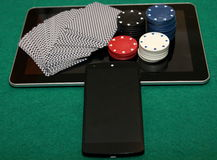 New era in online casino. 21st century casino - online casino. Deck of cards, chip, and mobile phone on the tablet royalty free stock images