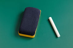 New eraser and chalk isolated on blackboard Royalty Free Stock Photos