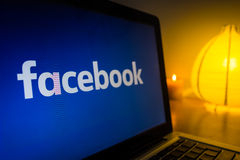 New facebook logo on a computer screen, turned on the light in the background royalty free stock photo