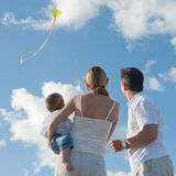 New Family Flies a Kite at the Beach with Baby. Parents with baby fly a kite in the sun against blue sky stock images