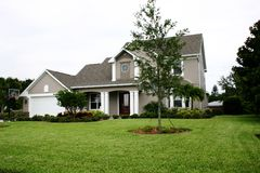 New Family Home on Acreage. New family home in suburbs with large green lawn, and young landscaping Stock Photography