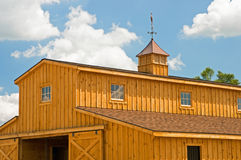 New farm barn with cupola. A view of a new wooden farm barn with weather vane on top of a cupola royalty free stock photo