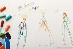 Hand drawn sketches for new fashion collection. New fashion collection background. Hand drawn sketches of clothes on white board, color swatches and threads, top Royalty Free Stock Photography