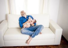 New father alseep while feeding his newborn baby Royalty Free Stock Photo
