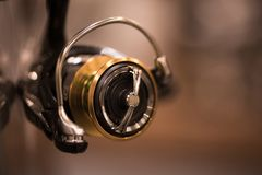 New fishing reel. Color close up shot of a new fishing reel with shallow depth of field stock images
