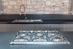 New fitted kitchen with built in gas hob. New fitted kitchen with stainless steel six burner gas hob detail royalty free stock photo