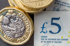 New five sterling pounds note and one pound coin Stock Image