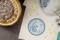 New five sterling pounds note and one pound coin Stock Photography