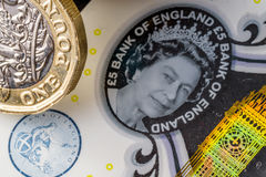 New five sterling pounds note and one pound coin Royalty Free Stock Photo
