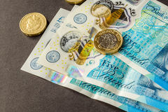 New five sterling pounds note and one pound coin Royalty Free Stock Photography