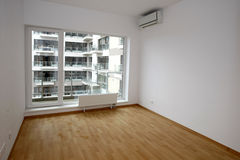 New flat. Empty room with hardwood floor in apartment building Royalty Free Stock Images