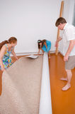 New floor covering. The grandmother, the son and the grand daughter unroll a new carpet covering in a sleeping room stock photography