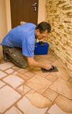 New floor tiles. A man working at a new floor tiles, cleaning them with water stock image