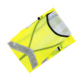 New florescent yellow safety vest. A new florescent yellow safety vest with silver reflective stripes folded on a white background Royalty Free Stock Photos