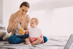 Careful babysitter holding a jar of baby food while feeding a toddler. New food. Cheerful attentive babysitter smiling while giving tasty fresh baby food to a stock images