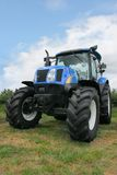 New Four Wheel Drive Tractor. New blue and black four wheel drive tractor standing idle in a field Royalty Free Stock Photography