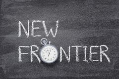 New frontier watch. New frontier phrase written on chalkboard with vintage precise stopwatch royalty free stock images