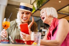 Positive aged woman showing her smartphone to a friend. New gadget. Positive aged women smiling while showing her new smartphone to a friend stock photo