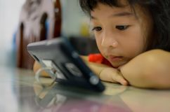 New Generation Kid using new technology to play or watch. A young girl, new generation kid playing a game or watching a movie or cartoons on a smart phone at royalty free stock image