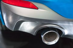 New generation of sportive mufflers. Oval Car Exhaust Tailpipe c. Hromed made of stainless steel on powerful sport car bumper. Close up Royalty Free Stock Image