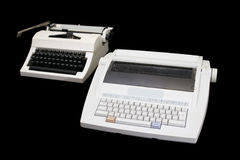 New generations. Two white typewriters of different generations on a black background royalty free stock photography