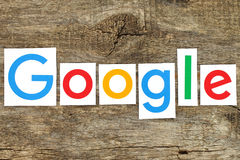 New Google logotype on old wood. Kiev, Ukraine - January 12, 2016:New Google logotype printed on paper, cut and placed on old wood.Google is USA multinational royalty free illustration