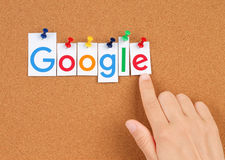 New Google logotype printed pinned on cork bulletin board with hand Royalty Free Stock Photography