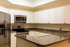 New Granite Counter And Stainless Appliances In White Kitchen Royalty Free Stock Images