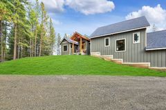 New gray wooden country house exterior with green grass stock image