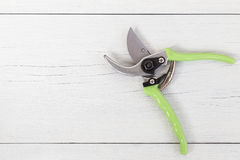New green secateurs on white wooden. Top view. New green secateurs on white wooden background. Top view Royalty Free Stock Photography