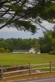 New Hampshire barn framed by trees and field royalty free stock image