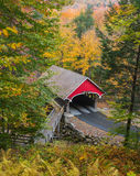 New Hampshire Covered Bridge. The red covered wooden bridge across the Pemigewassett River in the White Mountains of New Hampshire stands out aginst colorful royalty free stock photo