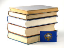 New Hampshire flag with pile of books isolated on white backgrou Royalty Free Stock Image