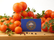 New Hampshire-Flagge auf einer Holzverkleidung mit den Tomaten lokalisiert auf a Lizenzfreies Stockbild