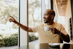 New happy summer day. Young confident African man enjoying his morning coffee and french croissant while sitting at stock photo