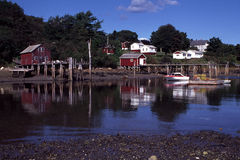 New Harbor, Maine at Low Tide. Shoreline reflections in New Harbor, Maine at low tide with red and white structures lining the water's edge and wooden piers Stock Photography