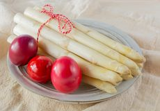 New harvest of white asparagus and colored Easter eggs, high quality raw asparagus in spring season, ingredients for Easter dinner. Close up stock photo
