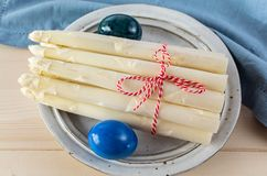 New harvest of white asparagus and colored Easter eggs, high quality raw asparagus in spring season, ingredients for Easter dinner. Close up royalty free stock photography
